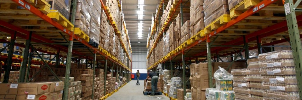 Warehouse of stock stacked to ceiling with a worker in background
