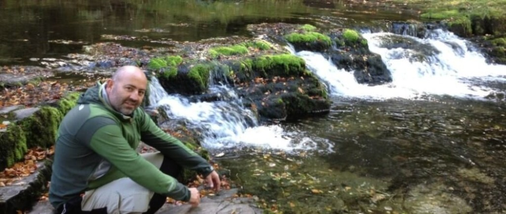 Chris Evans the founder of Waterfalls Ways, sat next to a waterfall