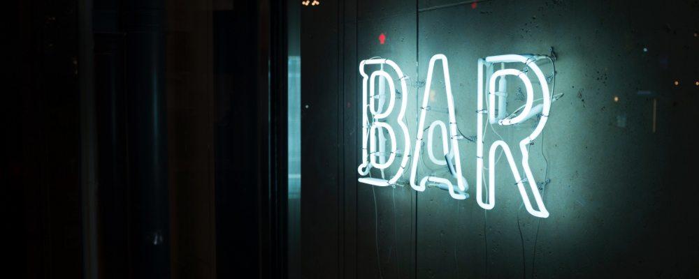 An illuminated neon bar sign