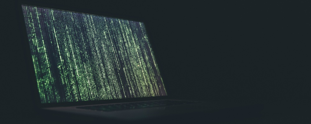 A laptop screen with the matrix symbols running across the screen