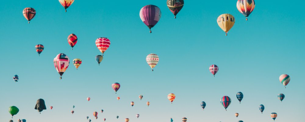 A bright blue sky full of hot air balloons