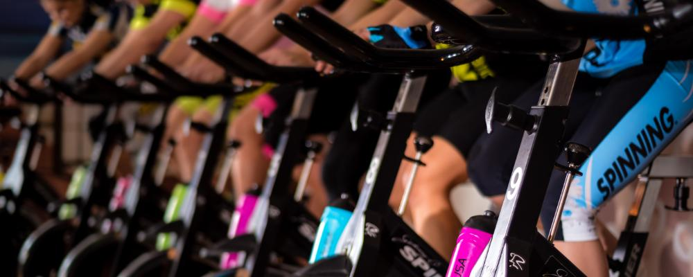 A row of spinning bikes in a gym