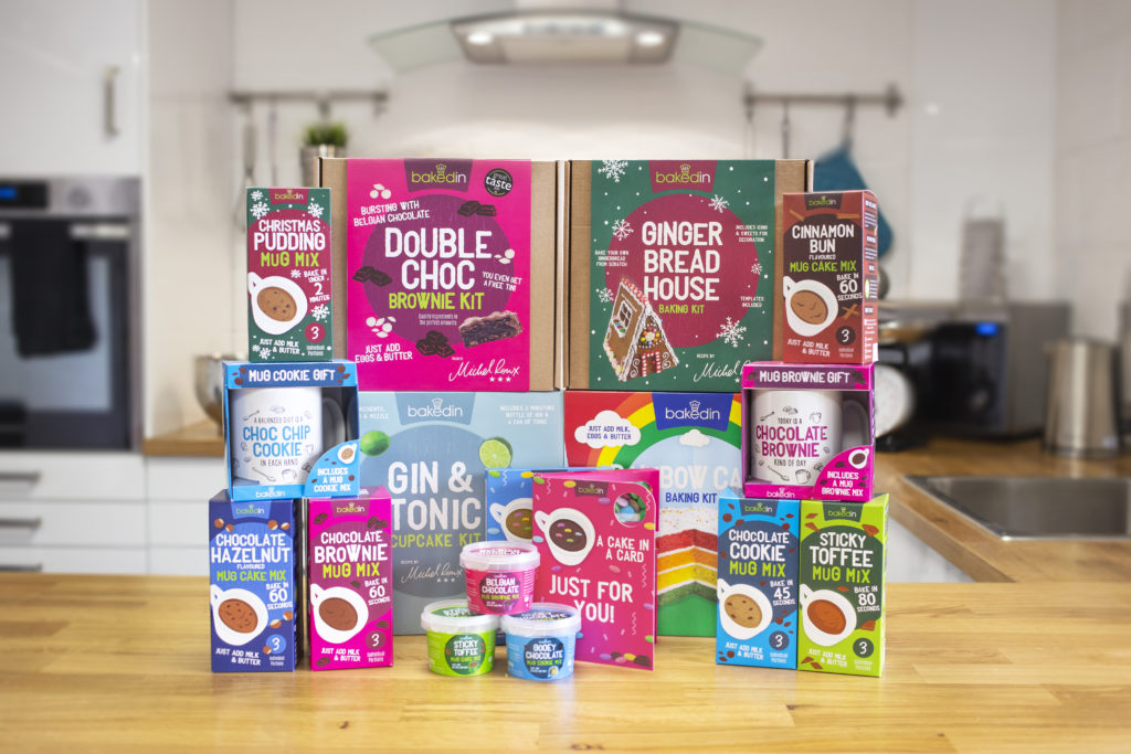 A range of BakedIn products in their colourful packaging arranged and stacked on a table