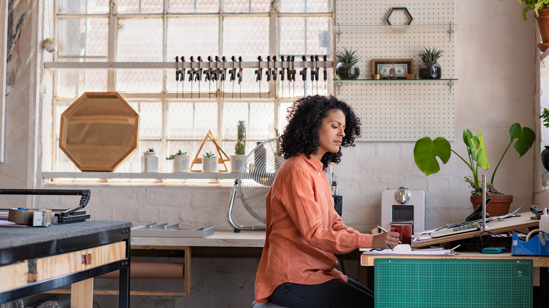 woman sat at desk in workshop
