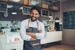 A smiling young coffee shop owner inside his premises