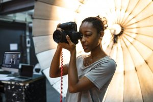 Young Black female photographer standing in front of a reflective umbrella