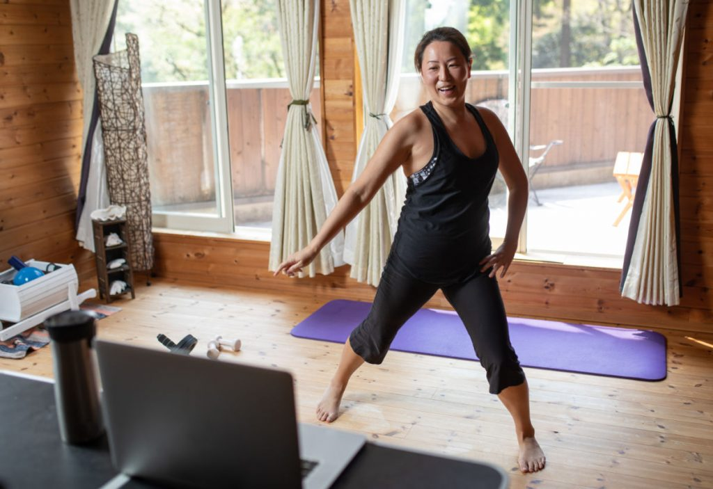 A woman doing aerobic exercises while staying at home