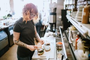 A woman works in her small modern coffee shop, preparing sandwiches to accompany the espresso drinks she serves