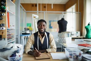 Young Black male cheerful fashion designer sitting by table in his workshop and making new sketches in notepad