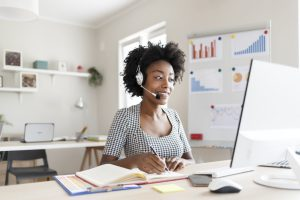 Female African American Customer Support Operator With Headset. Caller or Receptionist Phone Operator. Copy Space. Helping, Answering, Consulting. Happy Smiling African American Female Customer Support Phone Operator at Workplace