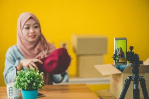 Young Muslim woman with hijab showing and review product in front of the smartphone to recording video and live streaming at home Online clothing store. Online marketing packaging delivery, startup SME entrepreneur or freelance woman concept. Small business owner.