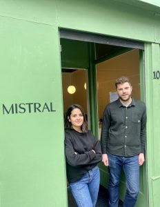 A man and woman standing outside of a Mistral shop