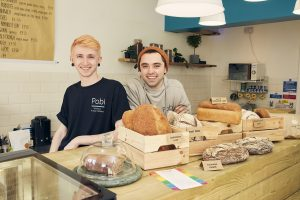 2 men from Pobi bakery stood behind a bread counter