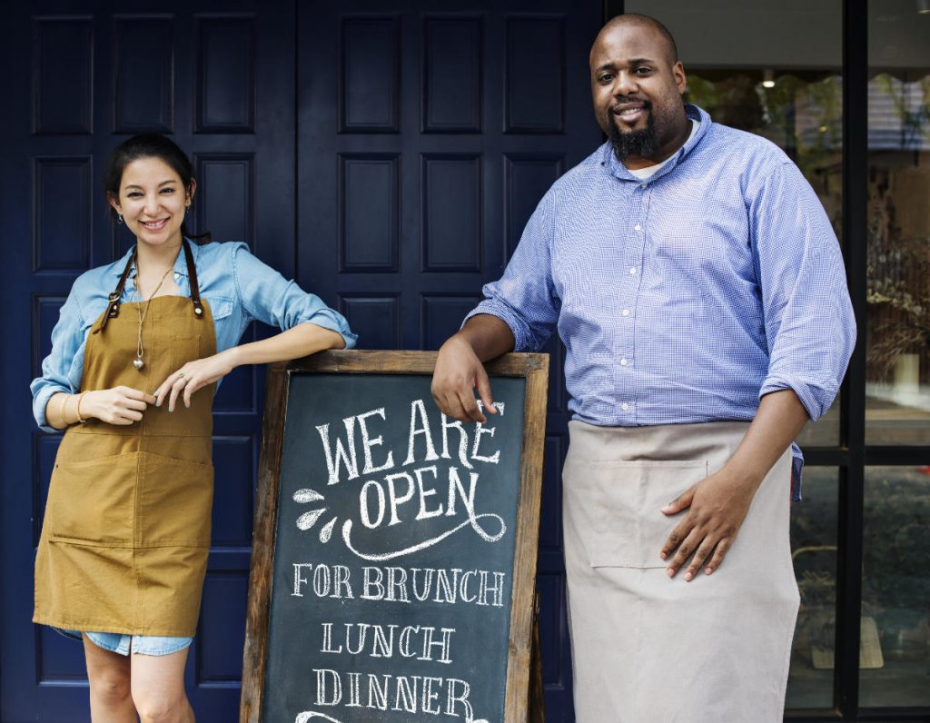 Two business owners, one male and one female, stand next to an open blackboard displaying information about their business opening hours and offering