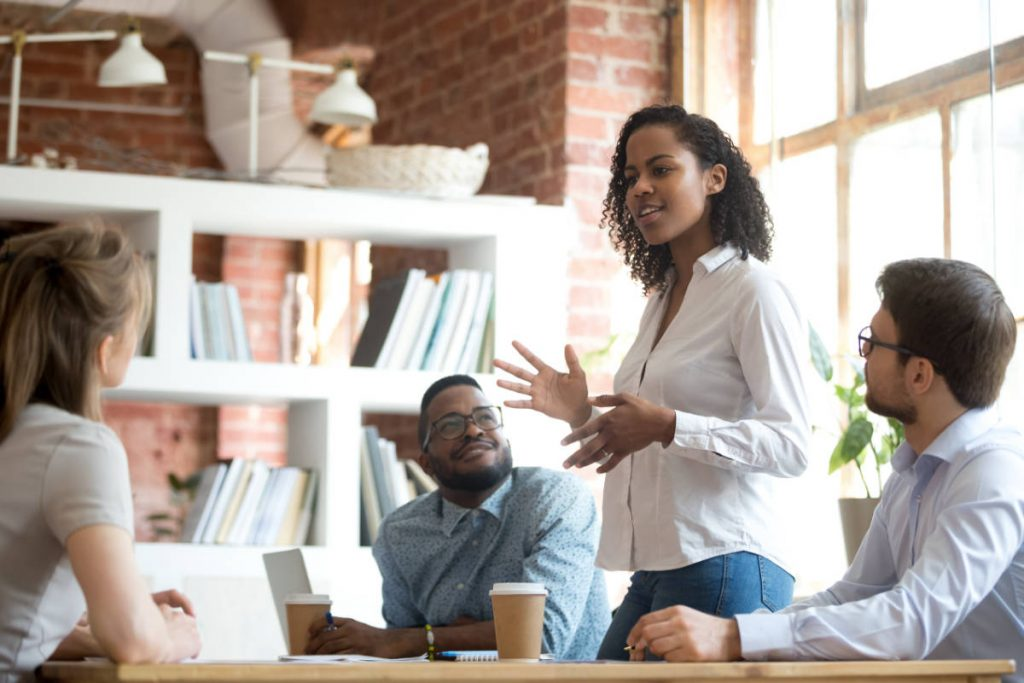 Ambitious smart african black female employee speaking at diverse meeting share creative idea opinion at group briefing while jealous envious skeptical male coworkers looking listening to colleague