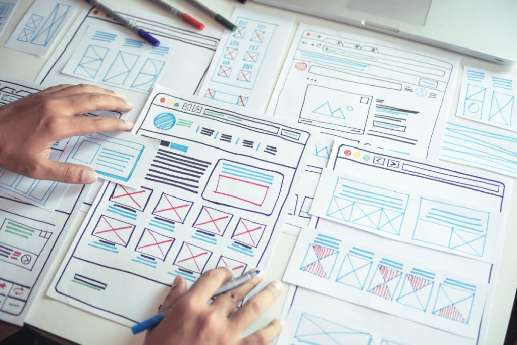 Website designer drawing a prototype as a wireframe design