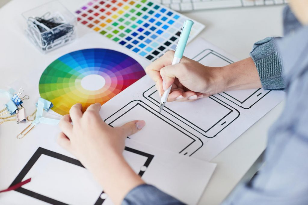 Close-up of designer's hands as they draw the design of the interface for a phone app