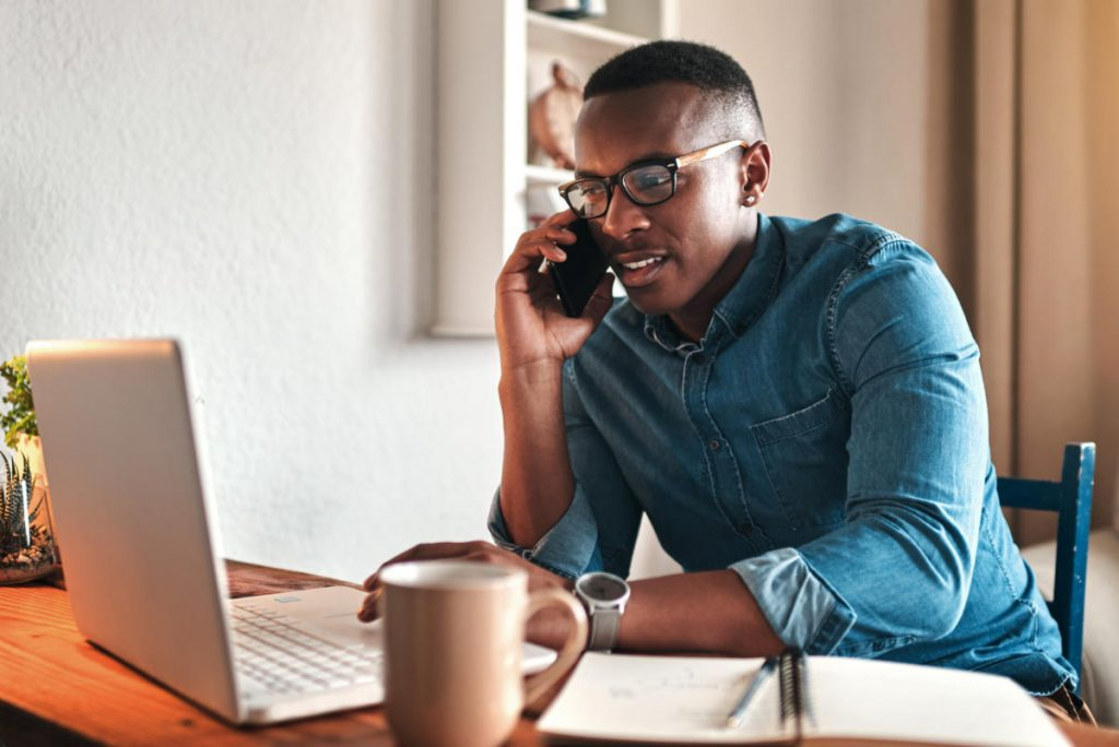 A handsome young Black businessman sitting alone in his home office and talking on his mobile