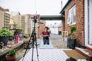 A mixed-race mid-adult female yoga instructor hosting an online class on her smartphone from her backyard