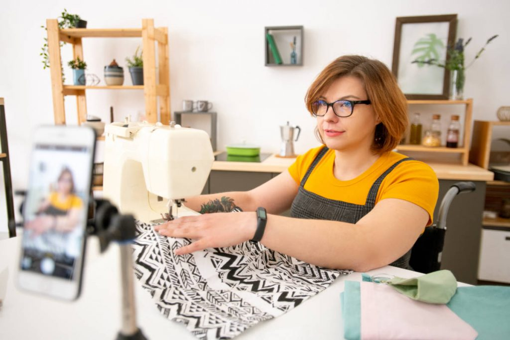Disabled young dressmaker in eyeglasses using sewing machine while giving online class on sewing