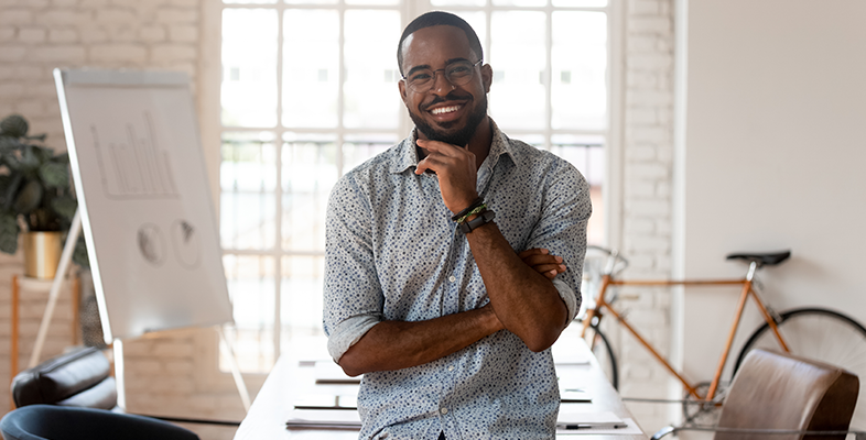Happy african american businessman entrepreneur startup owner stand in modern office looking at camera, smiling