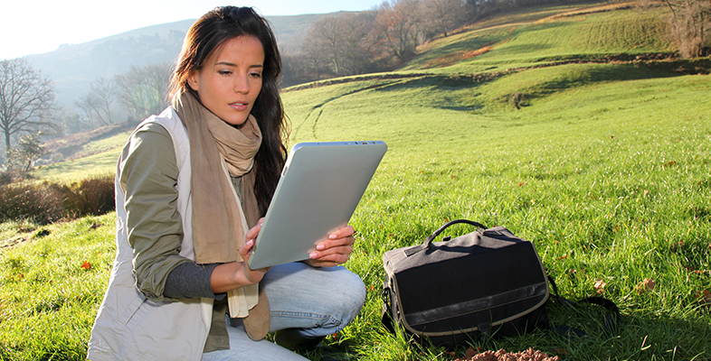 Female scientist looks at a tablet while sitting in the middle of open countryside