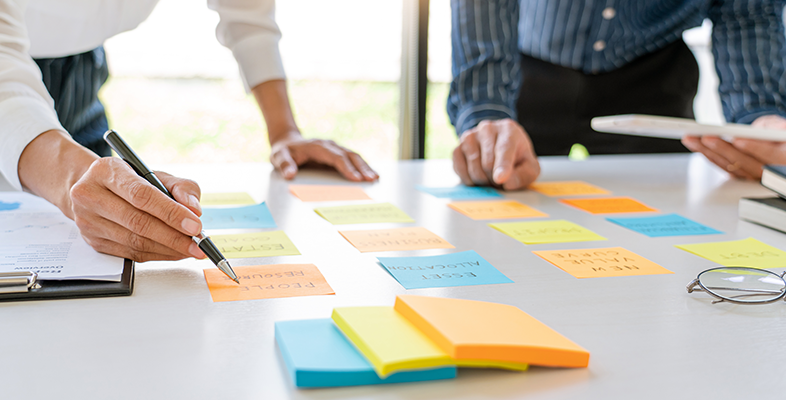 Young business workers brainstorming using multi-coloured post-it notes stuck to a large sheet laid on a desk in a modern co-working space